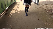 A girl walks on a dirt or sandy road with just socks without wearing shoes