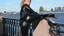 Latex Mona in a sexy suit and high heels walks down the street