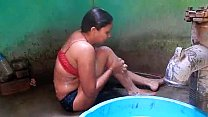Indian house wife bathing front of her husband صورة