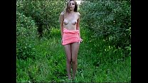 Young brunette outside in the field showing her young body