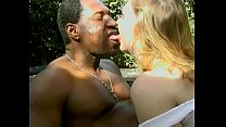 Black man is get ting French kiss from mature blonde chick sitting on the canvas slung chair