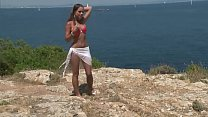 Chick in bikini strips by cliff
