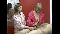 Senior masseuse helps junior masseuse in jerking off a naked client