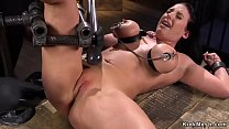 Tied busty slave in metal device bondage
