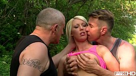Busty blonde babe Pamela sucks two cocks in the forest