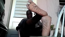 Bear black master shows his big feet after a day at work, he needs a slave.