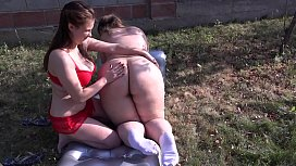 Busty lesbian licks hairy pussy at a fat girlfriend outdoors. Cunnilingus in the garden in the clearing.