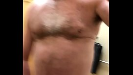 A naked daddy playing with his penis in a clothing store dressing room.