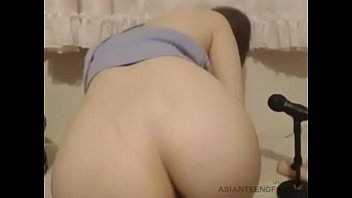 Busty Asian girl is fingering her shaved pussy on webcam at home