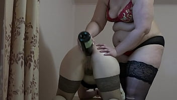 Anilingus and a bottle in anal. Fat mistress fucks obedient lesbian in the butt and licks her hairy asshole. Home role play and foot fetish.