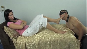Mistress Amelia plays with her slave while he is worshiping her feet thumbnail