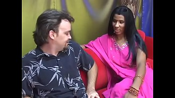 Young Indian lady gives an older man a blow job on a red couch