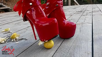 Lady L crush apples with extreme sexy red boots.