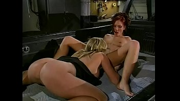 Hardcore lesbian scene with two sluts fucking in the back of a track in a garage