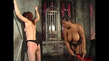 A mature ebony bitch with big jugs spanks a cute redhead babe on a juicy ass in the basement