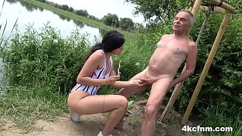 The young woman sucks the lollipop by the lake and rubs Santa's cock