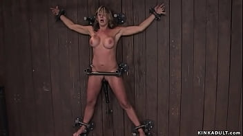 Busty MILF bound to the wooden wall