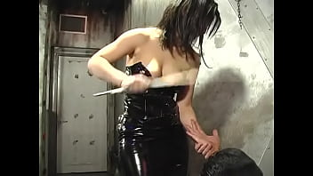 Busty chick in a latex dress ties a guy to the table and punishes him with a whip