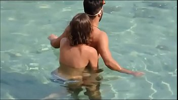 Girl gives her man a reacharound in the ocean at the beach