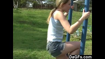 Young teen plays in the park and flashes her body