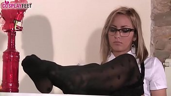 Schoolgirl in black dotted stockings plays with her feet