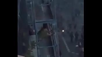 Mulher fudendo na sacada do prédio enquanto franceses manifestam