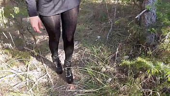 Walking on the wood wearing a black dress, pantyhose and high heels ankle boots