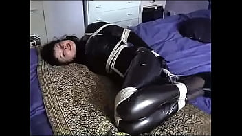Hogtied Beauty in Corset and Latex Struggles in Bed to Use Cellphone