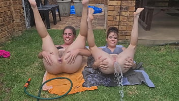 Half naked girls playing with a garden hose