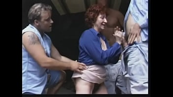 Dirty old slut grips and sucks two cocks at once