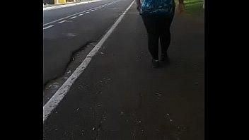 Coroa morena caminhando de calça legging preta