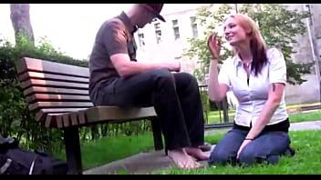 Submissive girl licks man'_s feet in park