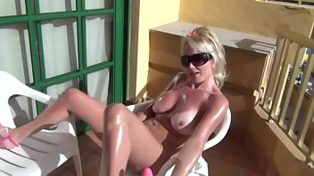 Christie gets oiled up and fucks herself on vacation balcony