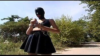 Blonde girl in latex dress walking in a country lane