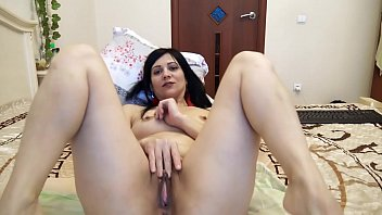 A hot brunette with a big pussy caresses herself in a wedding bed while her husband is away from home.