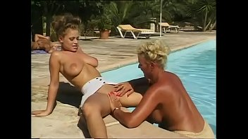 Two guys watching two lesbians in a pool, getting aroused