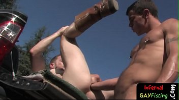 Submissive jock gets anally fisted outdoors