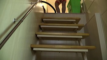 Sexy girl undresses on the stairs and masturbates hairy pussy with a dildo to orgasm.