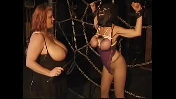 Redhead BBW with huge tits puts a closed mask on her slave's face and fondles her nipples hard