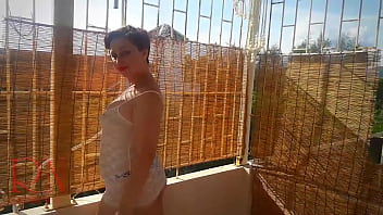 Wet t-shirt. Nude lady is getting shower outside on the top of hotel. Nude yoga