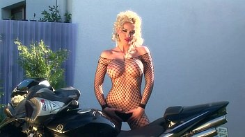 Busty blonde teases on a motorcycle in fishnet