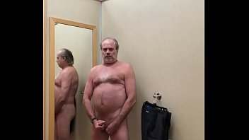 A naked daddy playing with his penis in a clothing store dressing room. video