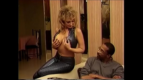 Luxurious blonde Nikki Sinn sucks a huge black cock at home in the living room