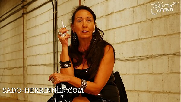 Mature Smoking Latex Mistress Herrin Carmen with PVC overknee boots is looking for personal ashtray Thumb