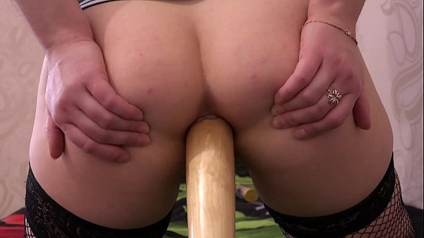 A girl in black stockings masturbates her ass with a baseball bat