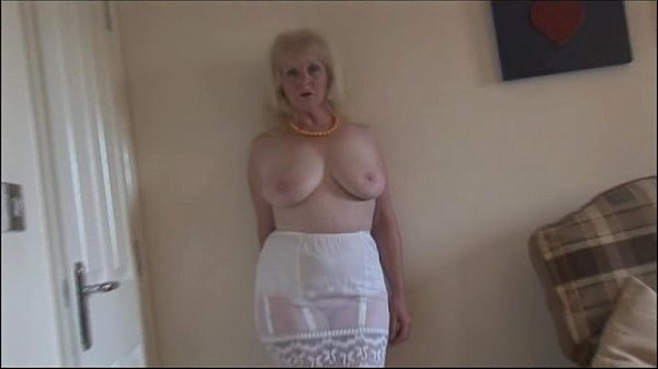 Mature busty lady in stockings and sheer slip s...