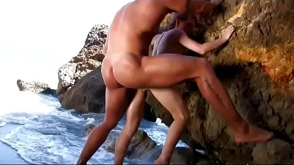 Muscly trainer bangs cute girl on the beach
