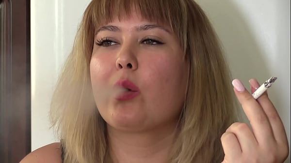 A beautiful BBW paints her lips with bright lipstick and smokes a cigarette. Homemade fetish and face close-up.