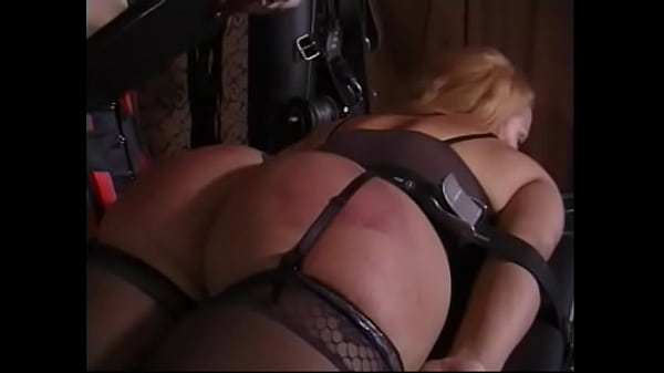A mature blonde in black stockings lies down on the table and lets her mistress spank her mouth-watering ass