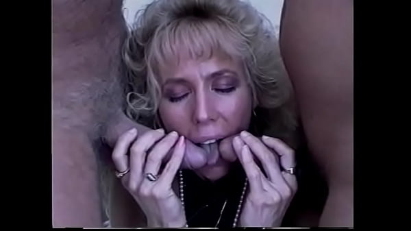 Busty blonde in a sexy swimsuit gives one guy a blowjob while his friend fucks her pussy in a dog pose